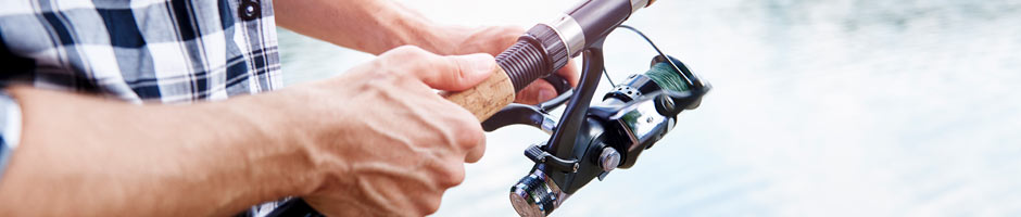 a close up image of a fisherman hands holding a rod while fishing a lake